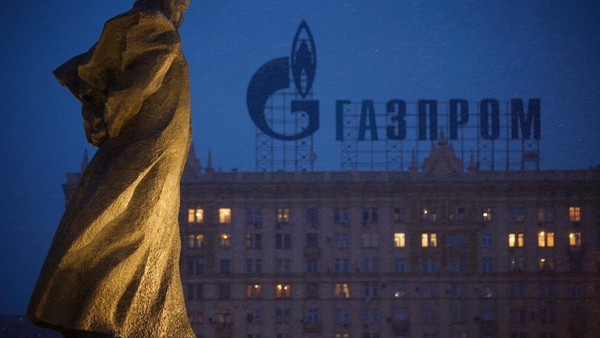 "FILE - In this Tuesday, March 4, 2014 file photo, a monument to Ukrainian poet and writer Taras Shevchenko is silhouetted against an apartment building with a sign advertising Russia's natural gas giant Gazprom, in Moscow, Russia. Poland has resumed deliveries of gas to Ukraine that it had halted after its own supplies from Russia dropped this week, the state pipeline operator said Friday, Sept. 12, 2014. The statement by Gaz-System S.A. suggests gas flows from Russian supplier Gazprom are once again meeting Poland's daily demand. State gas company, PGNiG, said that on Thursday it still registered some deficit compared to the ordered amount, but that the shortfall was lower than on Wednesday, when supplies were 45 percent short of demand. The spat between Poland and Russia came amid concerns that Moscow is ready to use its energy exports as a political weapon over the crisis in Ukraine.""We do not treat the situation as a crisis,"" Zawisza said. ""It is just one incident."" (AP Photo/Alexander Zemlianichenko, file)"