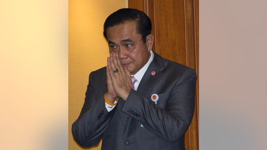"Thailand's Prime Minister Prayuth Chan-ocha gives a Thai tradition way of greeting ""wai"" before delivering his government's policy statement at parliament in Bangkok, Thailand Friday, Sept. 12, 2014. (AP Photo/Sakchai Lalit)"