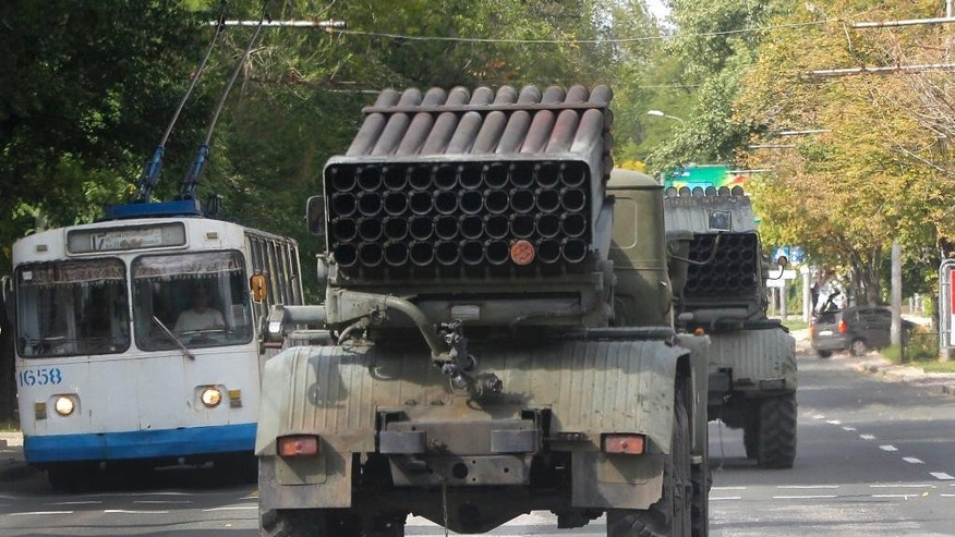 "Pro-Russian rebels drive multiple rocket launchers ""Grad"" (means ""hail"") in the town of Donetsk, eastern Ukraine, Thursday, Sept. 11, 2014. Two volleys of rocket fire rang out in Ukraine's eastern, rebel-held city of Donetsk, underscoring the difficulties of enforcing a cease-fire almost a week after it was signed. The city council of Donetsk confirmed in a statement Thursday there had been multiple explosions during the morning, but reported no casualties. ( AP Photo)"