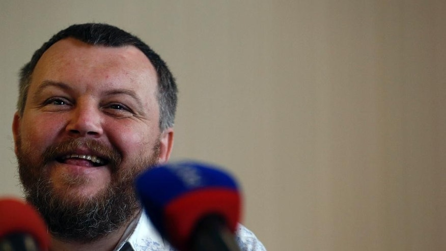 Pro-Russian rebel leader from eastern Ukraine Andrei Purgin smiles during a press conference in the town of Donetsk, eastern Ukraine,  Friday, Sept. 12, 2014. Government and rebel forces early Friday exchanged dozens of prisoners captured during fighting in Ukraine, as part of a cease-fire agreement sealed earlier this month. The transfer took place in the dark outside the main rebel stronghold of Donetsk under the watch of international observers. (AP Photo/Darko Vojinovic)