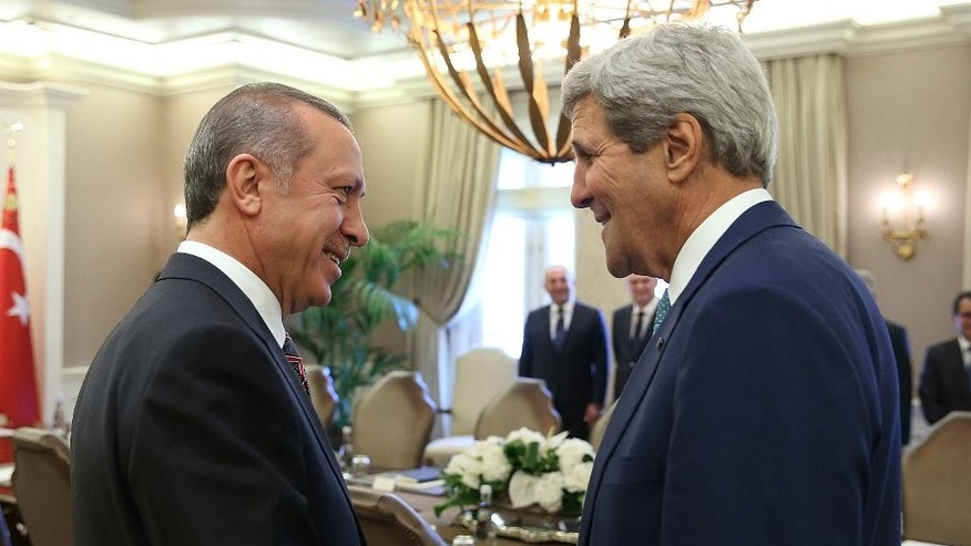 In this photo released by the Turkish Presidency Press Office, Turkish President Recep Tayyip Erdogan, left, and U.S. Secretary of State John Kerry speak before a meeting in Ankara, Turkey, Friday, Sept. 12, 2014. Kerry is in the region to speak with leaders about strategies to address the threat from the Islamic State, a militant extremist group. Secretary of State John Kerry said on Friday that the US would provide an additional $500 million in humanitarian aid to victims of the war in Syria, bringing total American assistance to $2.9 billion since the start of the conflict in 2011. (AP Photo/Turkish Presidency)