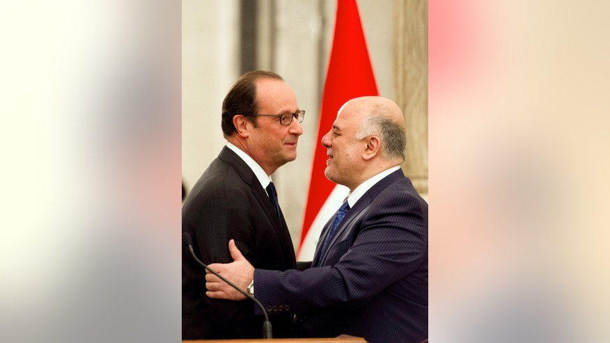 Iraq's new Prime Minister Haidar al-Abadi, right, and French President Francois Hollande hug during a press conference in Baghdad, Friday, Sept. 12, 2014. al-Abadi said France has agreed to take part in airstrikes as part of an expanding international effort to target the positions of militants with the Islamic State group. (AP Photo/Alain Jocard, Pool)