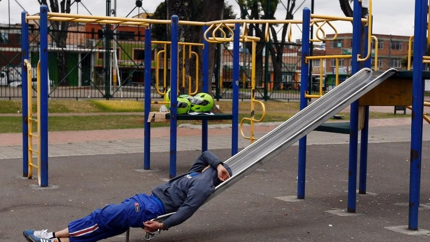 A detainee rests, handcuffed to a slide, at a children's playground in a public park in Bogota, Colombia, Thursday, Sept. 11, 2014. Due to overcrowding at a detention center located across the street, the park has been converted into makeshift holding area, where detainees, most accused of petty crimes, are kept for days waiting for a prosecutor's decision. (AP Photo/Fernando Vergara)