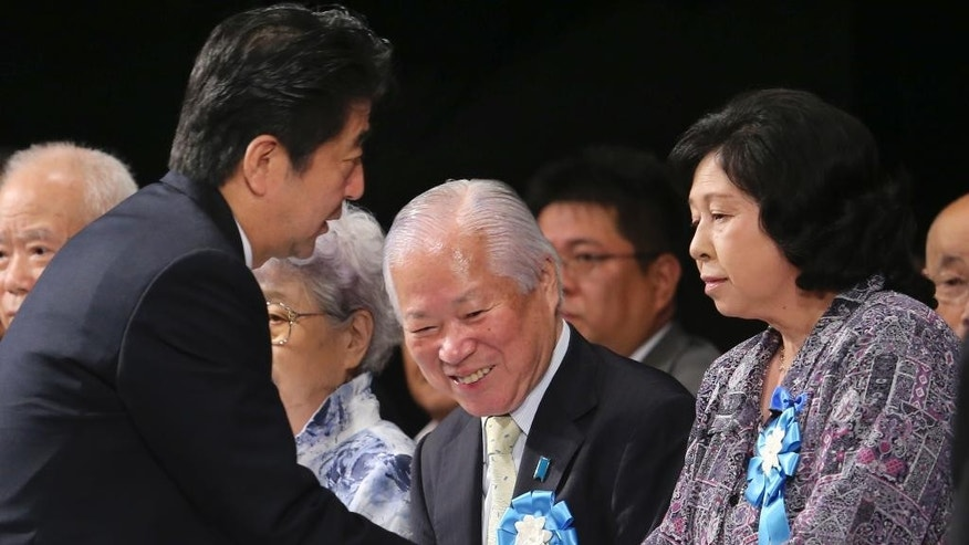 Japan's Prime Minister Shinzo Abe, left,  shakes hands with former abductee Hitomi Soga as Shigeru Yokota, center, father of Megumi Yokota who was also abducted by North Korean agents in 1977, looks on during a rally against North Korea's abductions, in Tokyo, Saturday, Sept. 13, 2014. Prime Minister Abe is turning up the pressure on North Korea to answer questions over the fate of possibly hundreds of Japanese citizens believed to have been abducted by the North's agents in the 1970s and 1980s. (AP Photo/Koji Sasahara)