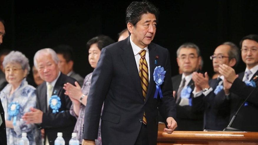 Japan's Prime Minister Shinzo Abe arrives for a rally against North Korea's abductions, in Tokyo, Saturday, Sept. 13, 2014. Prime Minister Abe told the rally in Tokyo on Saturday that he will not back down until every abductee is accounted for. Suggesting he believes some are still alive, he said he will not relent until they are allowed to come back to Japan. (AP Photo/Koji Sasahara)