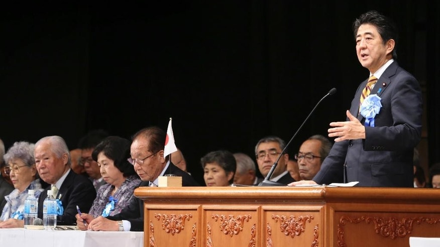 Japan's Prime Minister Shinzo Abe, right, delivers a speech during a rally against North Korea's abductions, in Tokyo, Saturday, Sept. 13, 2014. Prime Minister Abe told the rally in Tokyo on Saturday that he will not back down until every abductee is accounted for. Suggesting he believes some are still alive, he said he will not relent until they are allowed to come back to Japan. (AP Photo/Koji Sasahara)