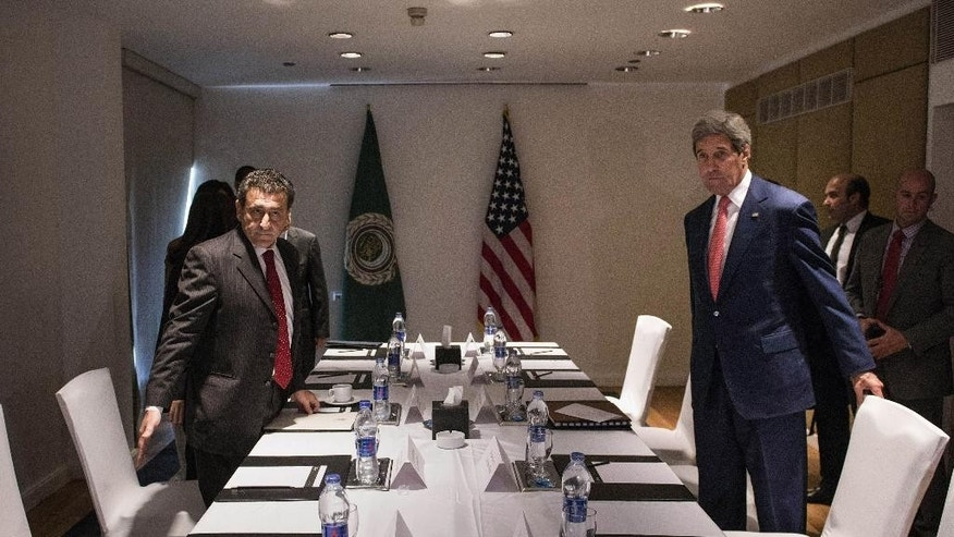 U.S. Secretary of State John Kerry, right, takes a seat before a meeting with Arab League officials in Cairo, Egypt, on Saturday, Sept. 13, 2014. Kerry arrived in Cairo for a short visit of less than a day to discuss how Egypt can help in the fight against the Islamic State group. He has been on a regional trip to garner support for President Barack Obama's initiative to assemble a coalition of nations to go after the militant group. Kerry heads to Paris next for a meeting on how to support Iraq in its fight against the Islamic State group, which holds large parts of Iraq and Syria. (AP Photo/Brendan Smialowski, Pool)