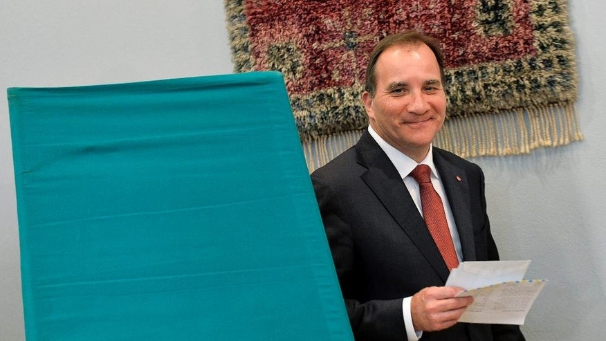 The leader of Sweden's Social Democrats, Stefan Lofven, votes at a polling station in Stockholm during the Swedish general elections, Sunday, Sept. 14, 2014. Sweden's parliamentary election opened Sunday with polls showing the left-leaning Social Democrats poised to return to power after eight years of center-right rule. (AP Photo/TT, Jonas Ekstromer )   SWEDEN OUT