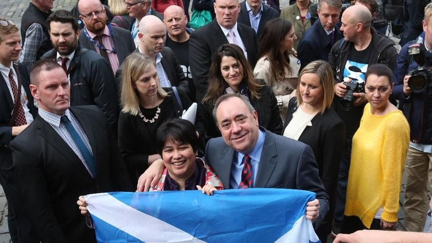 """In this photo taken on Tuesday, Sept. 9, 2014, First Minister Alex Salmond has his picture taken holding a Saltire flag as he meets with Scots and other European citizens to celebrate European citizenship and """"Scotland's continued EU membership with a Yes vote"""" at  Parliament Square in Edinburgh. (AP Photo/PA, Andrew Milligan) UNITED KINGDOM OUT, NO SALES, NO ARCHIVE"""