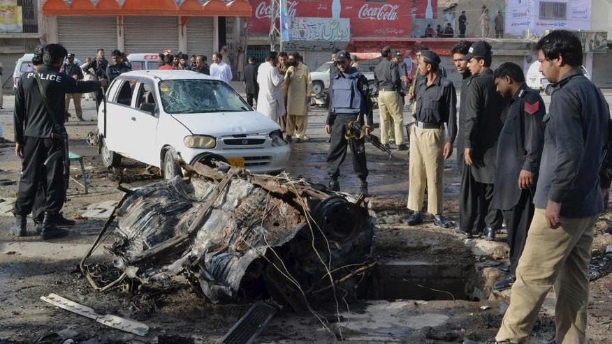 Pakistani police officers examine wreckage of a car at the site of a bomb explosion in Quetta, Pakistan, Saturday, Sept. 13, 2014. The powerful car bomb exploded in a bazaar in southwestern Pakistan, killing a few people and wounding tens, police said. (AP Photo/Arshad Butt)