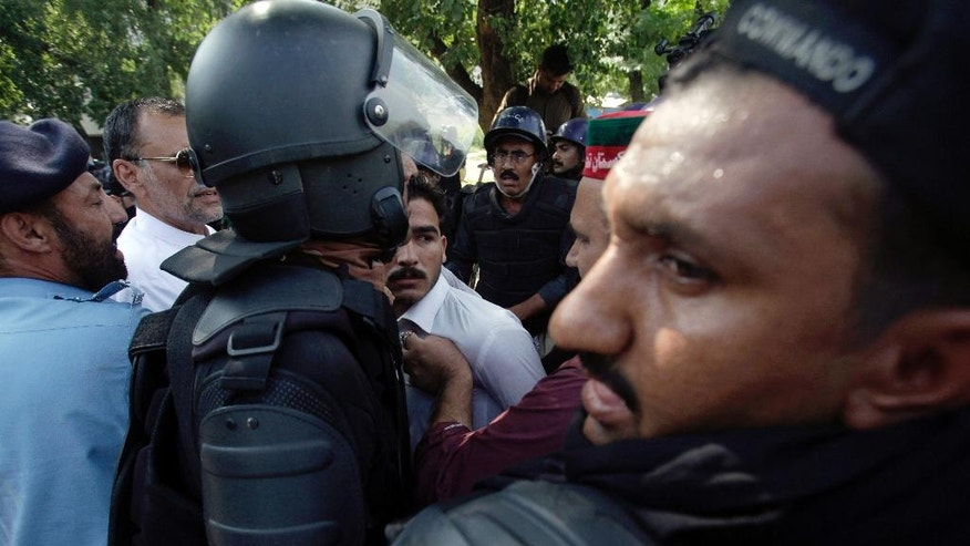 Pakistani police officers push anti-government activists who try to stop a prison van to free their detained colleagues in Islamabad, Pakistan, Saturday, Sept. 13, 2014. Pakistan's opposition said police have arrested scores of activists in an effort to stop them from participating in weekslong sit-ins in the capital, Islamabad. (AP Photo/Anjum Naveed)