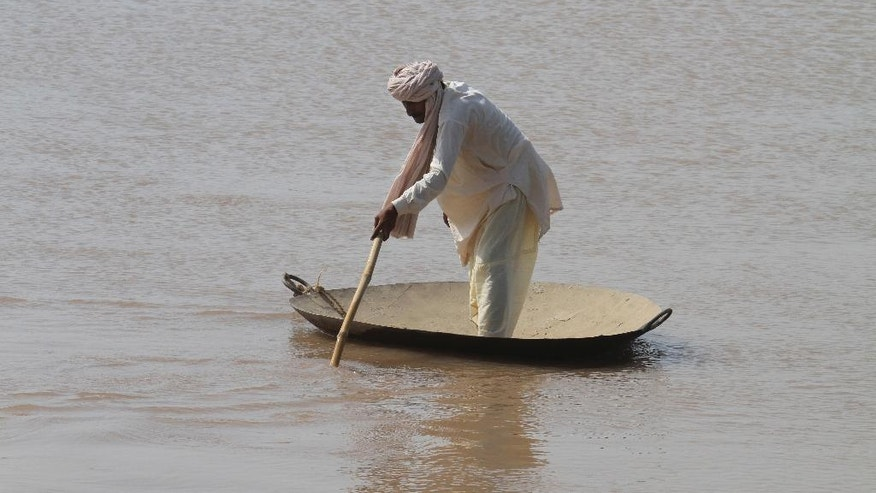 A Pakistani villager wades through floodwaters in district Shorkot near Jhang, Pakistan, Friday, Sept. 12, 2014. The Pakistani military stepped up rescue efforts as floods wreaked havoc in more districts of the country's eastern Punjab province on Friday, leaving hundreds of thousands a people homeless. After destroying hundreds of villages in the Jhang district this week, the floods on Friday hit three more Punjab districts. (AP Photo/K.M. Chaudary)