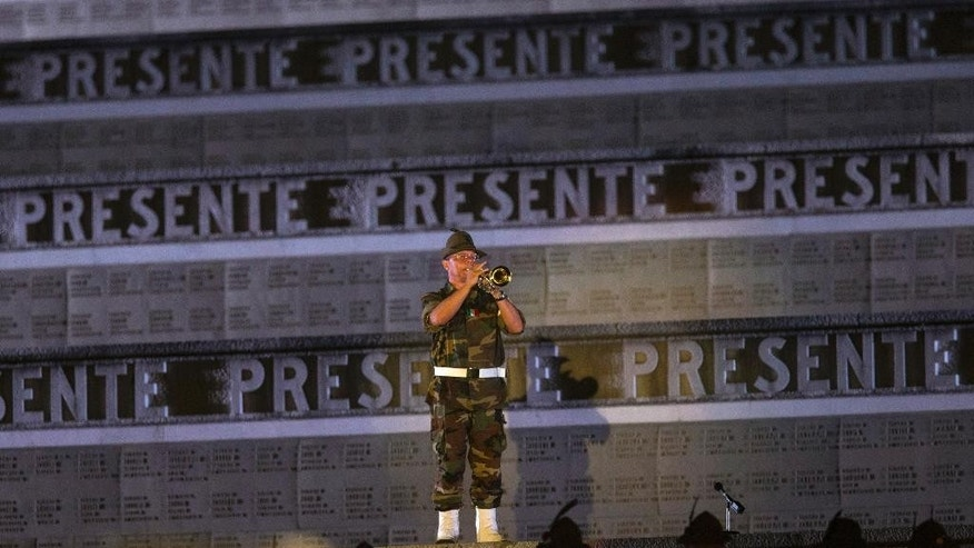 In this Sunday, July 6, 2014 file photo, an Italian Alpine soldier plays a homage with his trumpet to the fallen soldiers of World War I, ahead of a concert conducted by Riccardo Muti, commemorating the 100th anniversary of the outbreak of World War I at the Redipuglia memorial in Northeastern Italy.  The largest Italian war memorial, Redipuglia encases 100,000 Italian soldiers killed in battle, 60,000 of those whose identity remains unknown and 40,000 who are identified, sometimes with just an initial. (AP Photo/Paolo Giovannini, File)