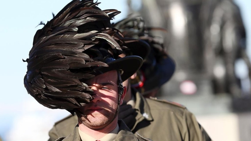 In this Nov. 26, 2013 file photo, the feathered hat of an Italian Bersagliere is blown by a strong wind as he stands at attention before the meeting in Trieste, Italy. In a personal moment, during a commemoration ceremony on Saturday, Sept. 13, 2014, the parents of an Italian soldier killed in Afghanistan last year will present Pope Francis with the distinctive feathered Bersagliere cap worn by the Piemontese corps famed for their endurance. (AP Photo/Luca Bruno, File)