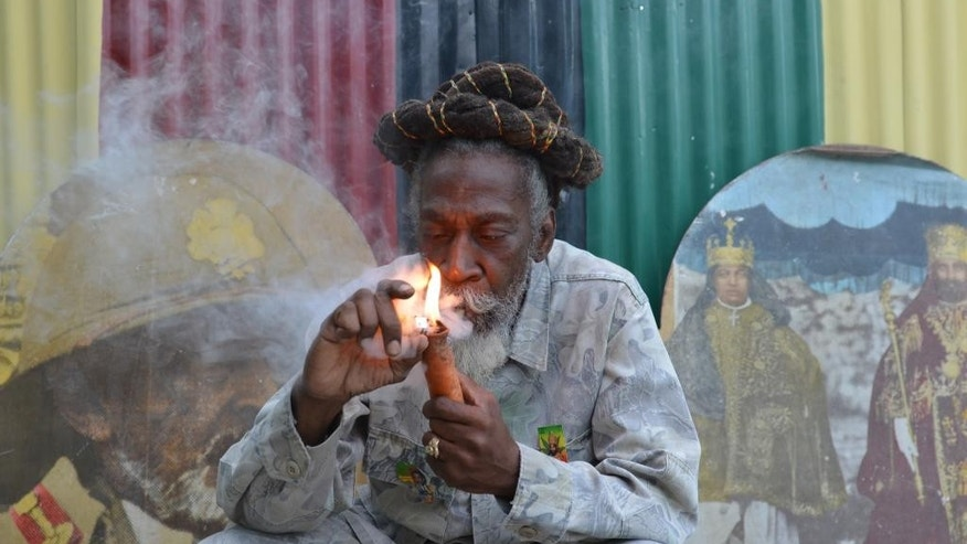 "In this Aug. 28, 2014 photo, legalization advocate and reggae legend Bunny Wailer smokes a pipe stuffed with marijuana during a ""reasoning"" session in a yard in Kingston, Jamaica, decorated with Rastafarian colors and images of former Ethiopian Emperor Haile Selassie. Wailer, a founder of the iconic Wailers reggae group with late superstars Bob Marley and Peter Tosh, and fellow Rastafarians have long called for legalization of the drug that they smoke as part of their spiritual worship. Now, many Rastas are welcoming plans by the Jamaican government to decriminalize marijuana for religious purposes, among other proposed amendments to the island's drug laws. (AP Photo/David McFadden)"