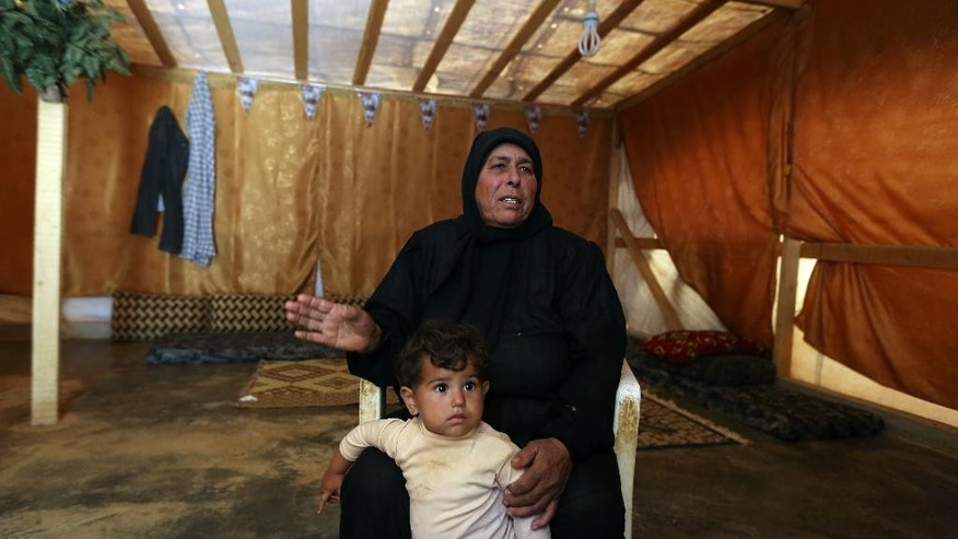 In this photo taken Wednesday, Sept. 10, 2014, Syrian woman Fatoum Allawi, 65, speaks during an interview with The Associated Press, as she holds her 15-month-old granddaughter Islam at a Syrian refugee camp in the village of Riyak in the eastern Bekaa Valley, Lebanon. Syrians like them are becoming victims of a wave of revenge attacks carried out after one of several Lebanese soldiers captured by militants from Syria in a cross-border raid was beheaded by jihadists earlier this month. The killing of the Shiite soldier by Sunni extremists has aggravated sectarian tensions in Lebanon, which is bitterly divided over the war in neighboring Syria. (AP Photo/Bilal Hussein)