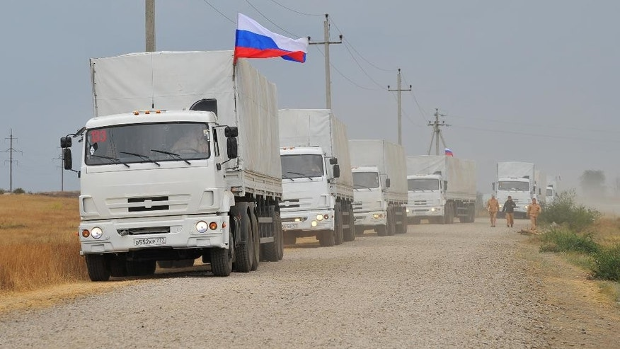 Russian trucks with Russian flags, intended to carry humanitarian aid for eastern Ukraine are stationed ready for another possible trip near Kamensk-Shakhtinsky, Rostov-on-Don region, Russia, Friday, Sept. 12, 2014. The ceasefire in eastern Ukraine has largely held. (AP Photo)