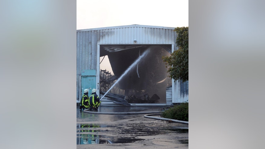 "Firefighters  try to extinguish a fire in a warehouse in Hilden,  Germany, early Sunday Sept. 14, 2014.  Police say four firefighters have been injured, three of them seriously, in explosions as they tackled a blaze at warehouses in western Germany.The fire in Hilden, near Cologne, broke out in the early hours of Sunday. Police said in a statement that the blaze expanded with ""several detonations"" after the firemen arrived at the scene. They say that packaging including paper and plastic, along with car tires, was stored at the site. Forty people were evacuated from nearby houses. The fire was under control after about five hours. ( AP Photo/dpa,Caroline Seidel)"