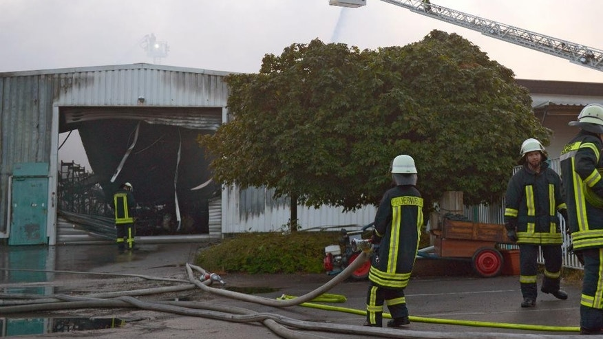 "Firefighters  stand outside  a warehouse in Hilden, western Germany, early Sunday Sept. 14, 2014. Police say four firefighters have been injured, three of them seriously, in explosions as they tackled a blaze at warehouses in western Germany.The fire in Hilden, near Cologne, broke out in the early hours of Sunday. Police said in a statement that the blaze expanded with ""several detonations"" after the firemen arrived at the scene. They say that packaging including paper and plastic, along with car tires, was stored at the site. Forty people were evacuated from nearby houses.The fire was under control after about five hours. (AP Photo/dpa,Caroline Seidel)"