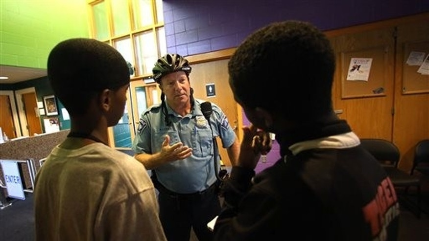In a July 16, 2014 photo, Minneapolis police officer Mike Kirchen talks with Mohamed Salat, left, and Abdi Ali at the Brian Coyle Center in Minneapolis. For the last year, the U.S. Department of Justice has been working with the city of Minneapolis to develop a national model of community policing within a community of color. Minneapolis beat out a bunch of cities for the opportunity for financial and analytical resources to improve relations and reduce crime. (AP Photo/The Star Tribune, Jim Gehrz)  MANDATORY CREDIT; ST. PAUL PIONEER PRESS OUT; MAGS OUT; TWIN CITIES LOCAL TELEVISION OUT
