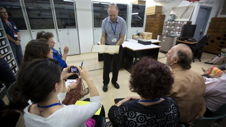 In this Monday, Sept. 8, 2014 photo, Yad Vashem's archive director Haim Gertner show's a document to visiting international experts and others who are participating in a workshop devoted to the physical and digital preservation of documents, in Jerusalem. With Holocaust survivors dying in growing numbers and their live testimonies soon to be a thing of the past, Holocaust commemoration efforts are increasingly focusing around preserving the belongings that contain their stories.  (AP Photo/Sebastian Scheiner)