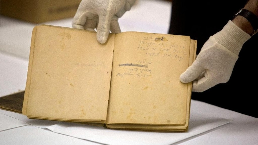 "In this photo taken Monday, Sept. 8, 2014, Yad Vashem archive director Haim Gertner show's a diary rescued from a burning synagogue on Kristallnacht - the notorious Night of Broken Glass in November 1938 when Nazi-incited riots marked the start of a campaign to destroy European Jewry, at the underground Yad Vashem Holocaust memorial archives in Jerusalem. During a tour for  international experts and others Gertner  read the following meticulously handwritten phrase: ""Memory is the only heaven from which you cannot be expelled."" (AP Photo/Sebastian Scheiner)"
