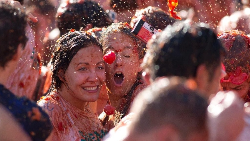 "A tomato is about to hit two women taking a selfie during a tomato fight in front of the Royal Palace turning Amsterdam's central Dam square into a red pulpy mess Sunday, Sept. 14, 2014. Entrepreneurs have seized upon Russia's boycott of European produce to set up a tomato-throwing fight. The idea is lifted from Spain's famed annual ""La Tomatina"" festival. The Dutch event is being marketed as a protest, but participants say they're mostly looking forward to smacking friends and strangers with overripe tomatoes. Wearing goggles is strongly advised. (AP Photo/Peter Dejong)"