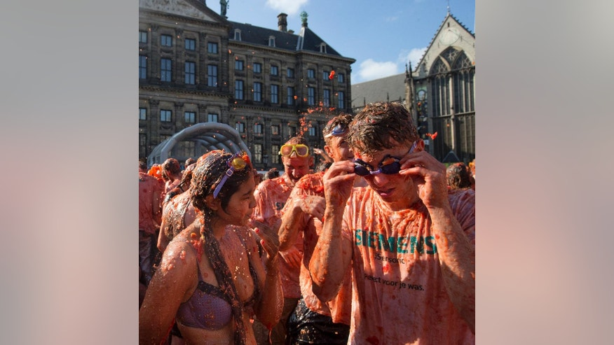 "Participants hurl tomatoes in front of the Royal Palace, rear left, turning Amsterdam's central Dam square into a red pulpy mess Sunday, Sept. 14, 2014. Entrepreneurs have seized upon Russia's boycott of European produce to set up a tomato-throwing fight. The idea is lifted from Spain's famed annual ""La Tomatina"" festival. The Dutch event is being marketed as a protest, but participants say they're mostly looking forward to smacking friends and strangers with overripe tomatoes. Wearing goggles is strongly advised. (AP Photo/Peter Dejong)"