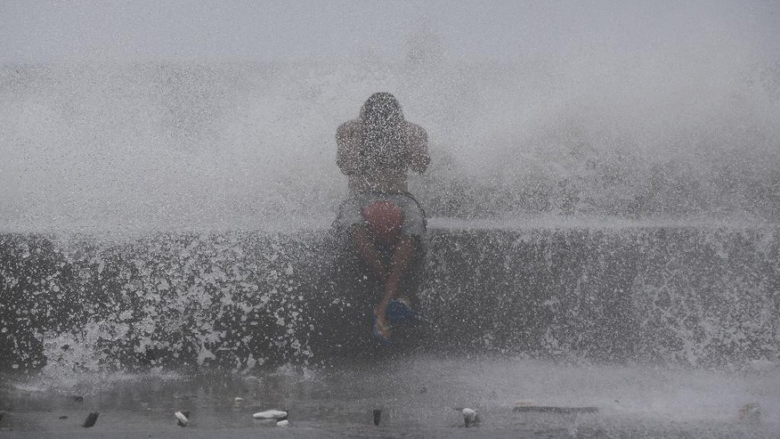 A Filipino reacts as he is hit by waves along a promenade in Manila, Philippines on Sunday, Sept. 14, 2014. The Philippine weather bureau says Typhoon Kalmaegi, locally called Luis, was located based on all available data at 266 km North Northeast of Virac, Catanduanes or at 347 km East Southeast of Casiguran, Aurora with maximum winds of 120 kph and gustiness of up to 150 kph. It is forecast to move West Northwest at 20 kph. (AP Photo/Aaron Favila)