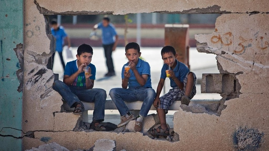 Palestinian school boys drink iced juice as they sit on a damaged wall of a school in Gaza City's Shijaiyah neighborhood, Sunday, Sept. 14, 2014. Some half million Gaza children made a delayed return to school on Sunday after a devastating 50-day war with Israel that killed more than 2,100 Palestinians and damaged hundreds of school buildings. (AP Photo/Khalil Hamra)