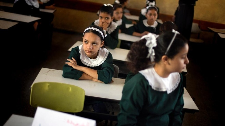 "Palestinian school girls sit in their classroom, as a paper with Arabic wring that reads,"" martyr Ghada Sobhi Ayyad,"" the name of a student who was killed during the war , is placed at her empty seat in a classroom at a school in Gaza City's Shijaiyah neighborhood, Sunday, Sept. 14, 2014. Some half million Gaza children made a delayed return to school on Sunday after a devastating 50-day war with Israel that killed more than 2,100 Palestinians and damaged hundreds of school buildings. (AP Photo/Khalil Hamra)"