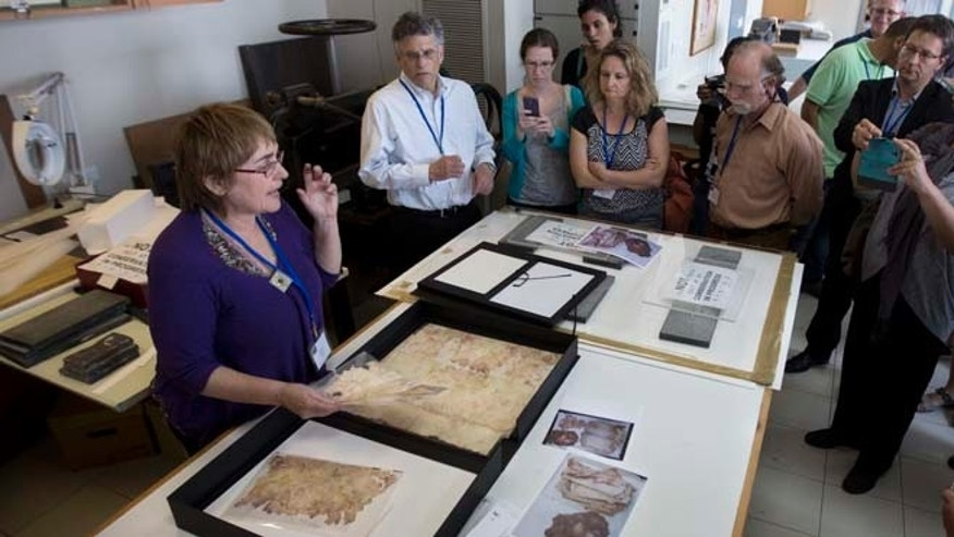 Sept. 8, 2014: In this photo, a worker shows restored documents at the Yad Vashem Holocaust memorial paper conservation laboratory to visiting international experts and others participating in a workshop devoted to the physical and digital preservation of documents, in Jerusalem. (AP)