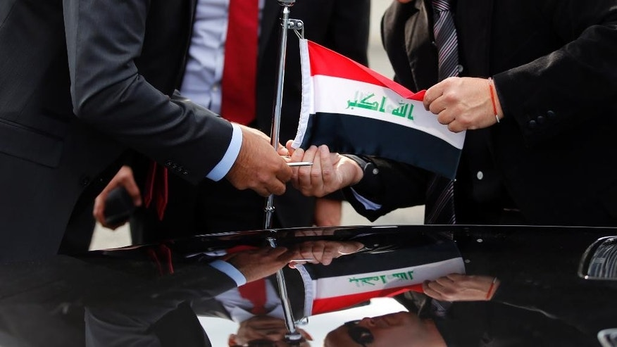 Officials install an Iraq flag on the car upon the arrival of Iraq President Fouad Massoum, and Iraq Foreign Minister Ibrahim Al-Jaafari at Orly airport south of Paris, France, Sunday, Sept. 14, 2014 ahead of a conference with U.S. Secretary of State John Kerry, French President Francois Hollande and diplomats from around the world. On Monday, Paris will host international talks seeking a strategy against the militants in Iraq, where they have overrun hundreds of miles of land in the country's north and west. (AP Photo/Francois Mori)
