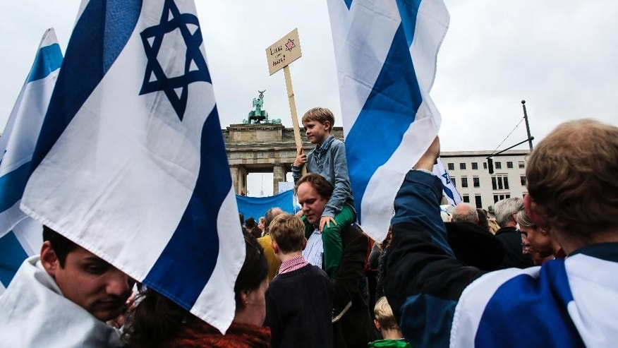 People with Israeli flags and banners attend a rally against anti-Semitism near the Brandenburg Gate in Berlin, Sunday, Sept. 14, 2014.  Thousands of protesters attended  the public rally  organized  by Germany's Jewish community at the capital's Brandenburg Gate after tensions over the Gaza conflict spilled over into demonstrations in Europe that saw anti-Jewish slogans and violence. (AP Photo/Markus Schreiber)