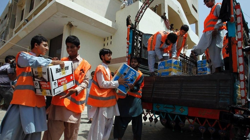 Members of an Islamic charity group Falah-i-Insaniat Foundation, load relief goods on to a truck going to flood affected areas, in Karachi, Pakistan, Sunday, Sept. 14, 2014. Civil and military officials have been using helicopters and boats to evacuate marooned people since Sept. 3, when floods triggered by monsoon rains hit Pakistan and Kashmir, which is divided between Pakistan and neighboring India. Hundreds of people have died in the flooding. (AP Photo/Fareed Khan)