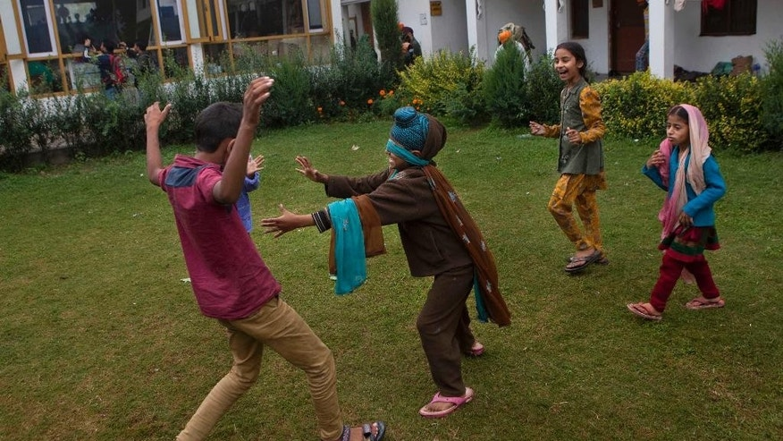 Children of Kashmiri flood victims play at a relief camp setup inside a Gurdwara or Sikh temple in Srinagar, Indian-controlled Kashmir, Sunday, Sept.14, 2014. About five thousand flood victims have taken refuge here. Military specialists blew up dikes in central Pakistan to divert swollen rivers and save cities from raging floods that have killed hundreds of people, authorities said Saturday, as officials stepped up efforts in India's part of Kashmir to prevent the spread of water-borne diseases there. (AP Photo/Dar Yasin)