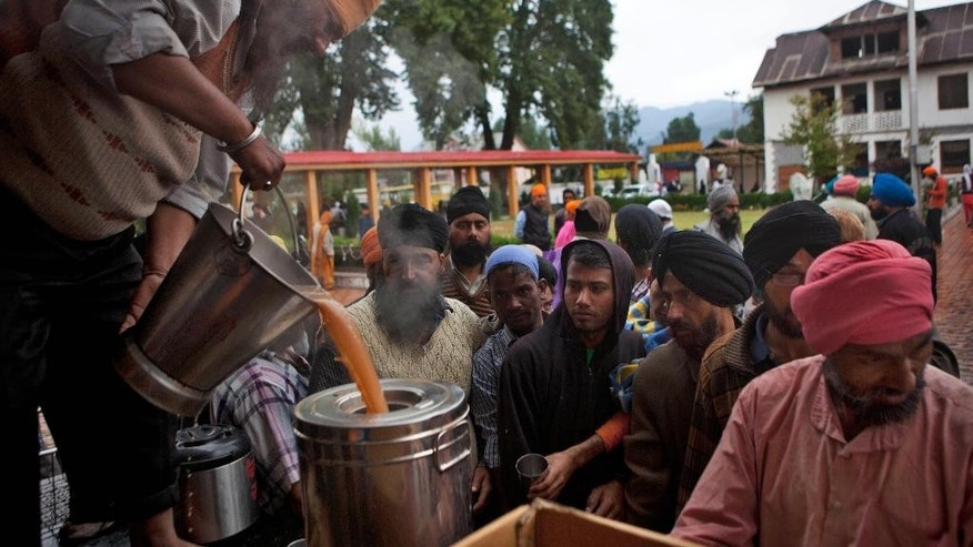 An Indian volunteer pours tea as flood affected people wait at a relief camp setup inside a Gurdwara or Sikh temple in Srinagar, Indian-controlled Kashmir, Sunday, Sept.14, 2014. About five thousand flood victims have taken refuge here. Military specialists blew up dikes in central Pakistan to divert swollen rivers and save cities from raging floods that have killed hundreds of people, authorities said Saturday, as officials stepped up efforts in India's part of Kashmir to prevent the spread of water-borne diseases there. (AP Photo/Dar Yasin)
