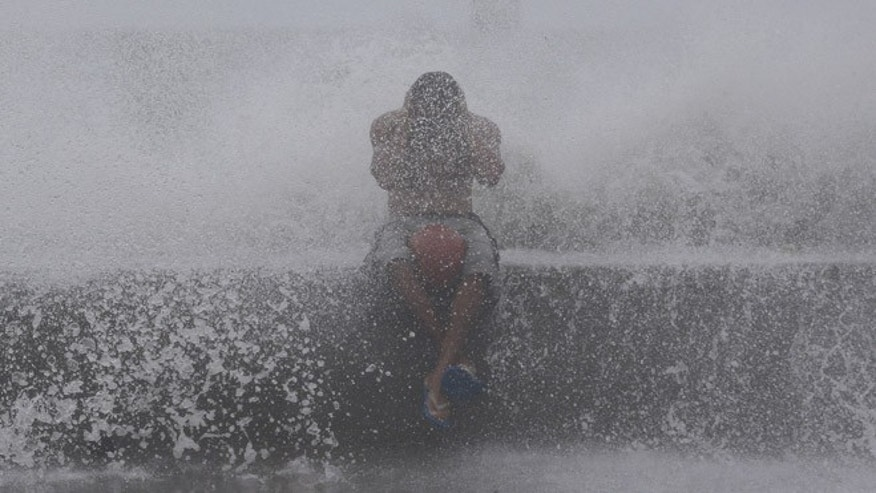Sept. 14, 2014: A Filipino reacts as he is hit by waves along a promenade in Manila, Philippines. (AP)
