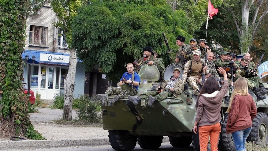 Residents wave to Pro-Russian rebels atop an armored personal carrier during a parade in the town of Luhansk, eastern Ukraine, Sunday, Sept. 14, 2014. Some semblance of normality is returning to parts of eastern Ukraine after a cease-fire agreement sealed between Ukrainian government forces and separatist rebels earlier this month, although exchanges of rocket fire remain a constant in some areas. (AP Photo/Darko Vojinovic)