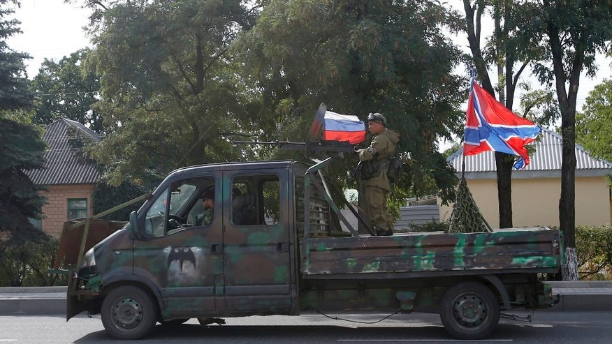 A Pro-Russian rebels truck with an anti-aircraft weapon attends a parade in the town of Luhansk, eastern Ukraine, Sunday, Sept. 14, 2014. Some semblance of normality is returning to parts of eastern Ukraine after a cease-fire agreement sealed between Ukrainian government forces and separatist rebels earlier this month, although exchanges of rocket fire remain a constant in some areas. (AP Photo/Darko Vojinovic)