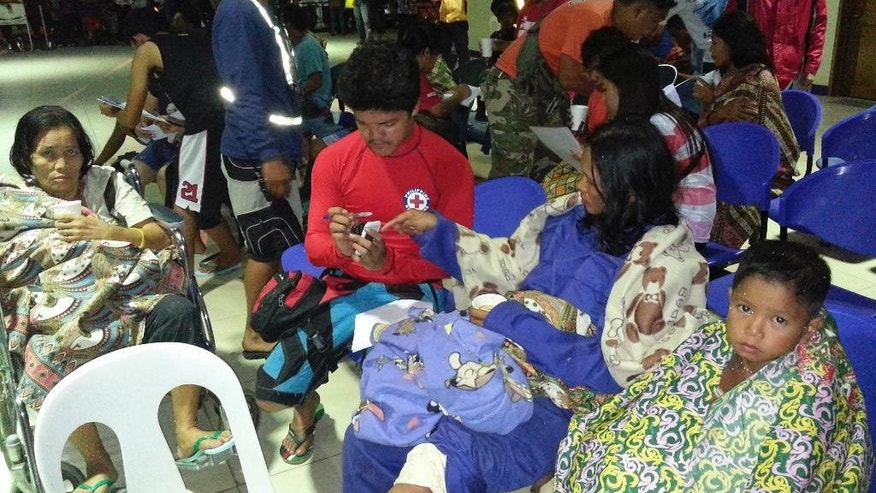 In this Saturday, Sept. 13, 2014 photo released by the Philippine National Red Cross Surigao Del Norte Chapter, survivors from the ferry M/V Maharlika II that sank after encountering steering problems, keep themselves warm with blankets as they arrive at the Lipata Port Terminal in Surigao city, central Philippines. Rescuers saved more than 100 people overnight and recovered at least three bodies from the ferry that sank in rough seas after encountering steering trouble in the central Philippines, officials said Sunday. (AP Photo/Philippine National Red Cross Surigao Del Norte Chapter)