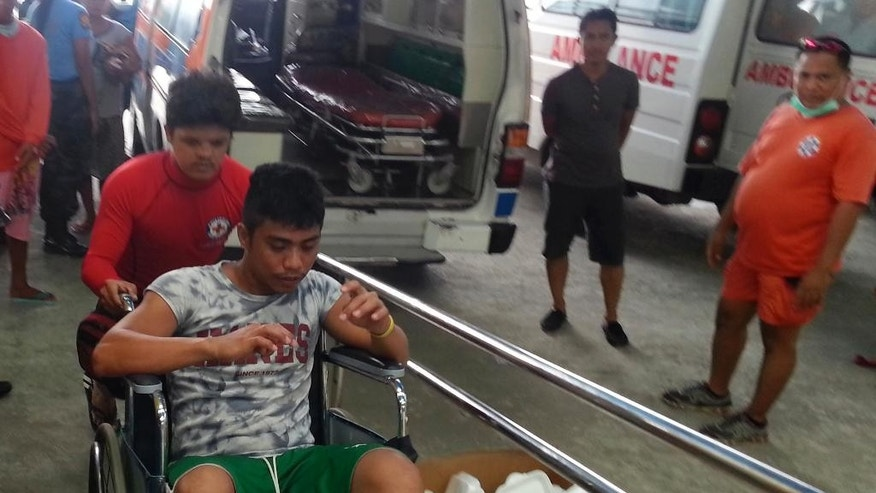 In this Saturday, Sept. 13, 2014 photo released by the Philippine National Red Cross Surigao Del Norte Chapter, a survivor from the ferry M/V Maharlika II that sank after encountering steering problems, is pushed on a wheelchair after arriving at the Lipata Port Terminal in Surigao city, central Philippines. Rescuers saved more than 100 people overnight and recovered at least three bodies from the ferry that sank in rough seas after encountering steering trouble in the central Philippines, officials said Sunday. (AP Photo/Philippine National Red Cross Surigao Del Norte Chapter)