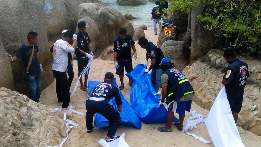 Sept. 15, 2014 - Thai officers work near the bodies of 2 British tourists on a beach in Surat Thani  province, southern Thailand. The bodies were discovered on a beach on Koh Tao, a small island known for its diving sites and serene beaches, police said.