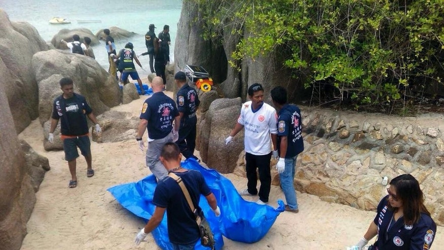Thai officers walk near the bodies of two British tourists Monday, Sept. 15, 2014 on a beach in Surat Thani  province, southern Thailand. Their bodies were discovered early Monday on a beach on Koh Tao, a small island known for its diving sites and serene beaches, police said. (AP Photo/Daily News) THAILAND OUT