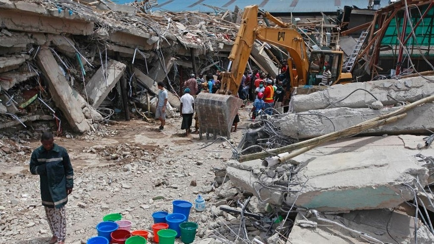 FILE-In this file photo taken on Saturday, Sept. 13, 2014, A rescue worker, left,  walks past buckets of water as the search for survivors continues in the rubble of a collapsed building belonging to the Synagogue Church of All Nations in Lagos, Nigeria. Rescue workers have recovered 46 bodies and rescued 130 survivors from a collapsed shopping mall and guesthouse at the campus of renowned Nigerian preacher T.B. Joshua's Synagogue Church of All Nations, the West African nation's emergency agency said Monday, Sept. 15, 2014. (AP Photo/Sunday Alamba, File)