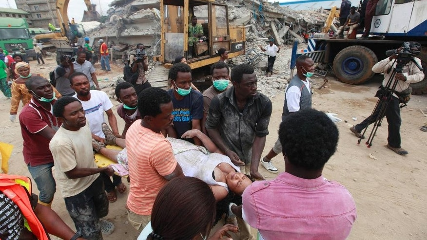 FILE-In this file photo taken on Saturday, Sept. 13, 2014, Rescue workers carry a survivor from the rubble of a collapsed building belonging to the Synagogue Church of All Nations in Lagos, Nigeria. Rescue workers have recovered 46 bodies and rescued 130 survivors from a collapsed shopping mall and guesthouse at the campus of renowned Nigerian preacher T.B. Joshua's Synagogue Church of All Nations, the West African nation's emergency agency said Monday, Sept. 15, 2014. (AP Photo/Sunday Alamba, File)