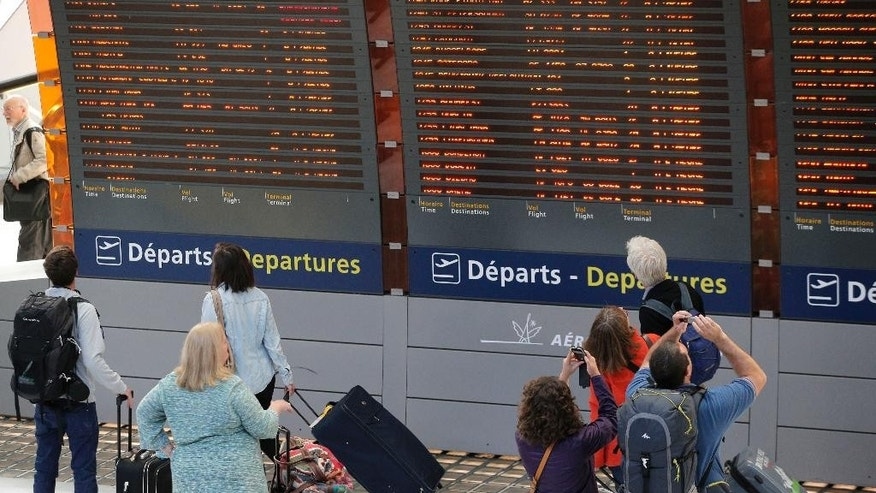 Travelers look at departure boards at Paris Charles de Gaulle Airport in Roissy, near Paris, Monday, Sept. 15, 2014. At least half of Air France flights around the world were canceled Monday as pilots kicked off a weeklong strike, angry that the airline is shifting jobs and operations to a low-cost carrier to better keep up with competition. (AP Photo/Christophe Ena)