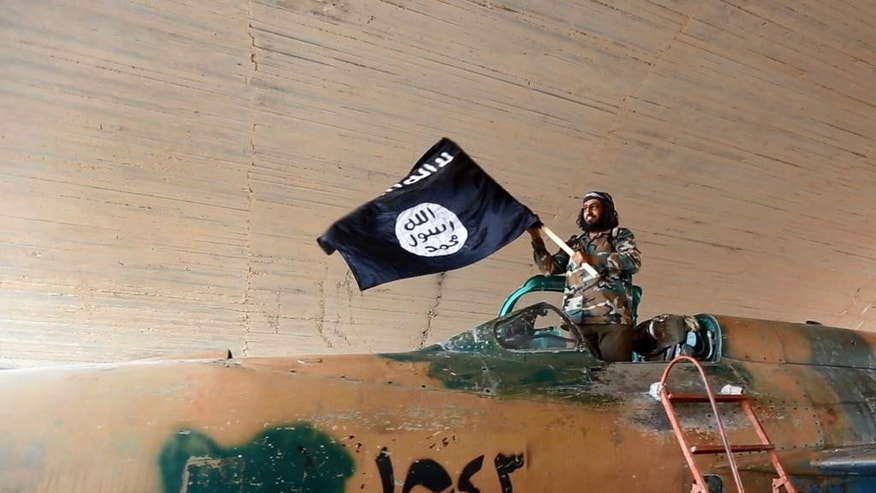 FILE - This undated file image posted on Aug. 27, 2014, by the Raqqa Media Center of the Islamic State group, which has been verified and is consistent with other AP reporting, shows a fighter of the Islamic State group waving their flag from inside a captured government fighter jet following the battle for the Tabqa air base, in Raqqa. Secretary of State John Kerry is to travel to the Middle East this week, with stops in Saudi Arabia and Jordan, to try to line up support for a coalition to take on the extremist Islamic State group. His trip follows Secretary of Defense Chuck Hagel's visit on Monday to Turkey to make the same case to Ankara, a regional heavyweight. Kerry will hold talks with officials from Jordan, Turkey and Egypt, as well as Saudi Arabia, Qatar, the United Arab Emirates and other Gulf nations. (AP Photo/Raqqa Media Center of the Islamic State group, File)
