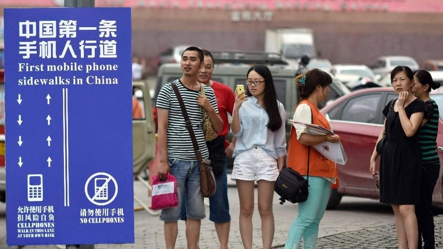 "Sept. 13, 2014 - Residents look at a sign with the words ""China's First Cellphone Lane"" in southwest China's Chongqing Municipality. The Chinese city created a sidewalk with a separate lane for those using smartphones, as a reminder not to tweet while walking the street."