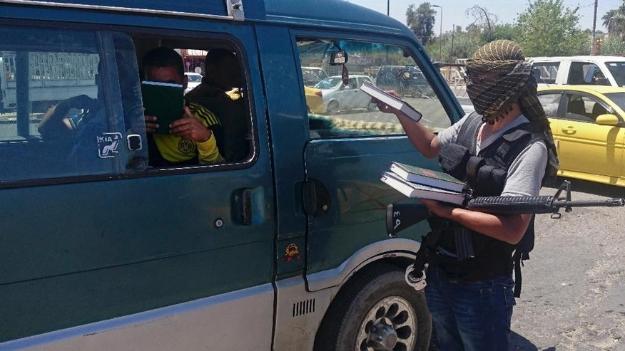 "FILE - In this Sunday, June 22, 2014 file photo, a fighter from the militant group who refer to themselves as the Islamic State, distributes a copy of the Quran, Islam's holy book, to a driver in  Mosul, 225 miles (360 kilometers) northwest of Baghdad, Iraq. The extremist-held Iraqi city of Mosul is set to usher in a new school year. But unlike years past, there will be no art or music, and classes about history, literature and Christianity have been ""permanently annulled."" (AP Photo, File)"